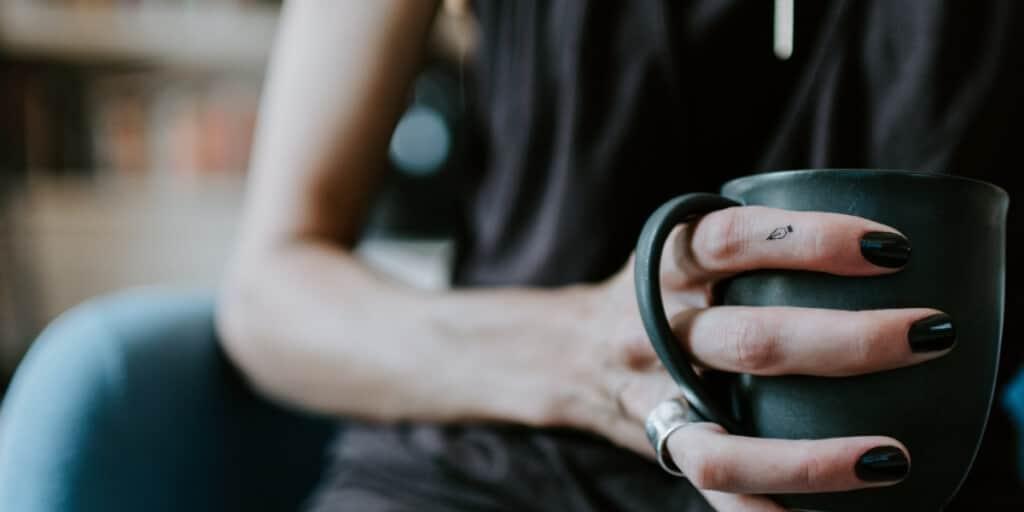 Kleines Füllfederspitzen-Tattoo auf dem Finger