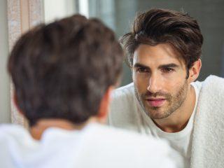 Der Mann schaut in den Spiegel