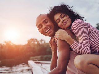 Glückliches junges Paar umarmt und lächelt and