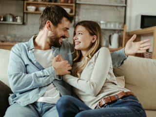 Liebevolles glückliches Paar, das zu Hause miteinander redet