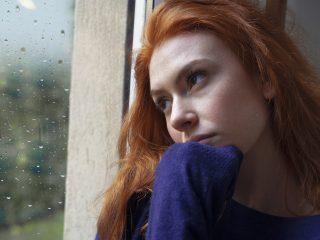 besorgtes Mädchen, das zu Hause durch das Fenster schaut