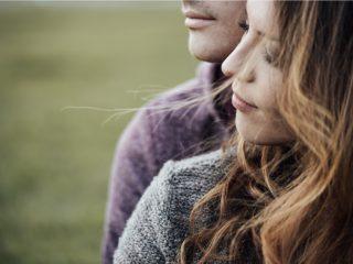 Junge liebevolle Paare, die draußen auf Gras sitzen