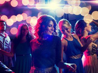 lächelnde Freunde tanzen im Club