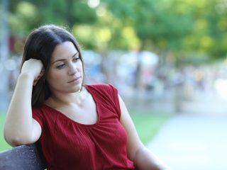 traurige Frau sitzt allein draußen