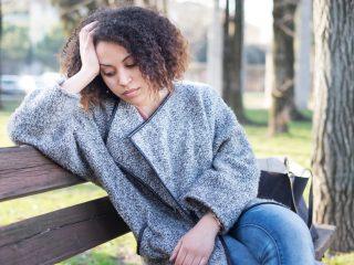 traurige Frau sitzt auf der Bank im Park