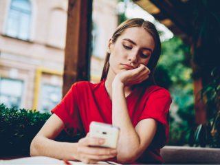 worried woman looking at mobile phone