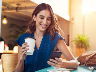 eine lächelnde Frau, die an einem Tisch sitzt und Kaffee trinkt und ein Telefon drückt
