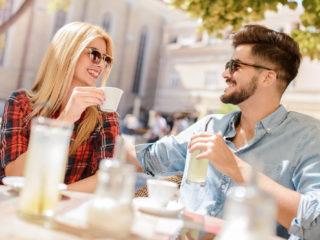 ein lächelnder mann und eine frau sitzen draußen und trinken kaffee