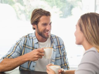 ein lächelnder Mann sitzt mit einer Frau und trinkt Kaffee
