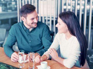 ein mann und eine frau sitzen zusammen und unterhalten sich beim kaffee