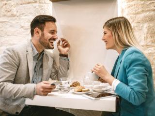 ein lächelnder mann und eine frau beim frühstück sitzen und reden