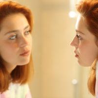 vor dem Spiegel denkt eine traurige rothaarige Frau