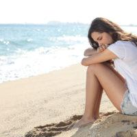 eine traurige frau, die am strand sitzt