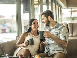 ein lächelnder Mann und eine Frau, die in einem Café auf der Couch sitzen und Kaffee trinken und reden